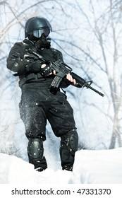 NATO soldier in winter uniform with the M4 machine gun on the forest background.
