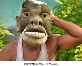 NATUN SAMAGURI SATRA, MAJULI, ASSAM, INDIA - OCT 26, 2017: An Assamese Vaishnavite mask-making artist shows his half-finished, unpainted religious face mask on Majuli Island, on Oct 26, 2017.
