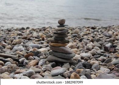 Natur, Steine gestapelt am Wasser. Stone Art on the Rhine. bunte Steine Kunst. Wasser im Hintergrund. This Scene 2 of 3