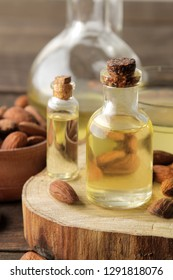 natural almond oil in a glass bottle and fresh almond nuts close-up on a brown wooden table.