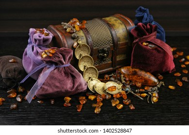 Natural amder, bijouterie and velvet pouches for jewelry on the dark wooden board.