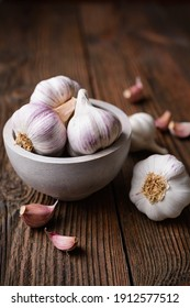 Natural antibiotic, fresh garlic bulbs with cloves on rustic wooden background
