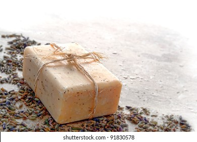 Natural artisan Marseilles style aromatherapy and body care bath soap bar tied with organic raffia twine over lavender seeds for a relaxing cleaning and hygiene bath