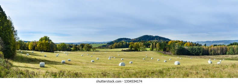 Natural autumn panorama. Green meadow, trees, mountains and blue sky. Grassland with hay packaged in round white plastic wraps. Panoramic landscape with look on Hradistsky hill. South Bohemia, Europe.