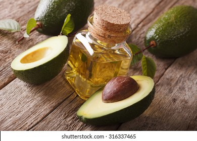 natural avocado oil in a glass bottle on a wooden table close-up, horizontal