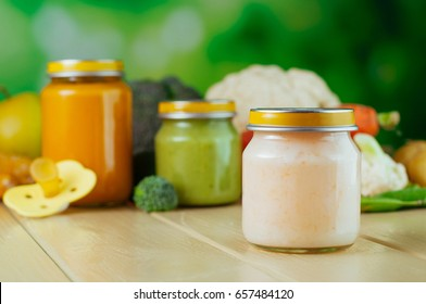 Natural baby food concept: jars with vegetable puree on the light wooden background near broccoli, cauliflower, potato, carrot, apple; selective focus