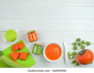 Natural baby food on the white wooden background: home made vegetable puree with pumpkin, squash and Brussels sprouts;  top view, copy space.