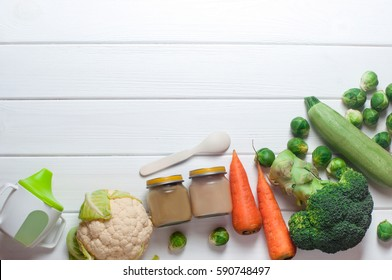 Natural baby food on the white wooden background: home made vegetable puree in glass jars with squash, cauliflower, carrot, broccoli and Brussels sprouts; top view, copy space