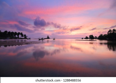 Natural background of the colorful sky and beautiful water reflection during sunset at Mae Ramphueng Beach ,Prachuap Khiri Khan province in Thailand