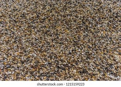 Natural background of small colored pebbles on the beach