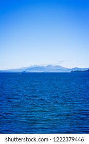 Natural background - volcanic cones of Ruapehu towering over great lake of Taupo on a beautiful sunny day. North Island Volcanic Plateau, New Zealand