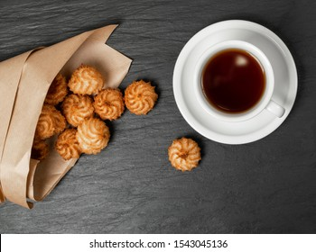 Natural baked coconut cookies or cocoanut macaroons with tea or coffee. Homemade diet biscuits with coco chips on black stone background top view