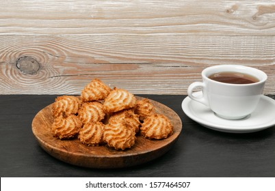 Natural baked coconut cookies or cocoanut macaroons with tea or coffee. Homemade diet biscuits with coco chips on wooden plate side view