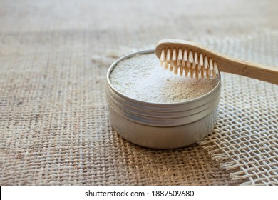 Natural bamboo toothbrushes and kaolin dentifrice or tooth powder made from natural ingredients on rustic background with copy space. Sustainable lifestyle, bathroom essentials in zero waste home