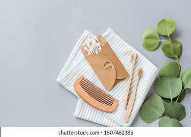 Natural bathroom accessories: wooden comb, bamboo toothbrush, massage brush, ear sticks, eucalyptus on gray paper background. Zero waste products. Mockup, flat lay, template, top view, overhead