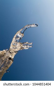 Natural beautiful transparent icicles looks like a hand hang on a clear winter day. Winter background with hanging icicles and blue sky