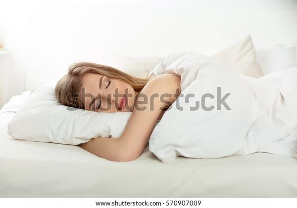Естественная красивая женщина, спящая в постели.