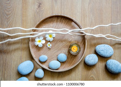 natural beauty, ayurveda spa or detox wellness with beautiful pebbles, candle, fresh flowers and twigs over round wooden tray and background, top view