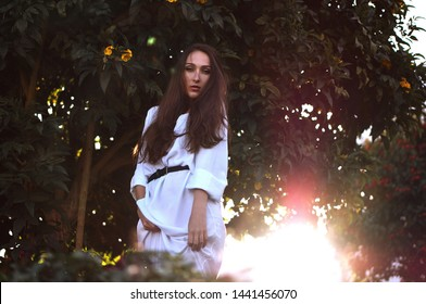 Natural beauty. Beautiful woman with long hair in traditional white dress among summer green garden with colorful flowers.