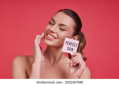 Natural beauty.  Beautiful young woman smiling and touching her cheek while standing against pink background