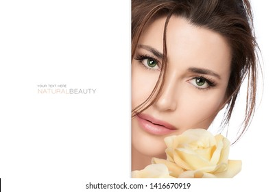 Natural beauty and bio cosmetics concept with a gorgeous green eyed woman wearing subtle makeup with a flawless skin holding a  yellow rose to her face in a half portrait with lateral white copy space