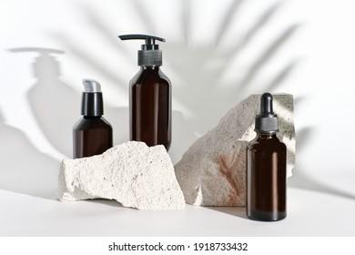 Naturkosmetikprodukte in unmarkierten braunen Flaschen. Sommerkleidung. Feuchtigkeitsspendende Öle und Lotionen für trockene Haut. Schatten aus Palmblättern. Probieren Sie Ihre Kosmetikmarke aus.