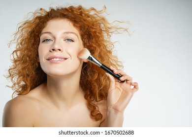 Natural beauty. Delighted red-haired female person expressing positivity while doing face contouring, preparing for meeting