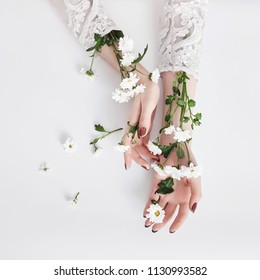 Natural beauty hand cosmetics with flower extract, product. Summer Fashion woman hand on the table with flower, skin care. Creative makeup, girl hands lying on the table, white background
