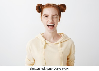 Natural beauty and people concept. Portrait of amazing emotive woman with red hair and two buns, showing tongue and winking at camera, being confident and sassy over gray background