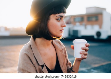Natural beauty pretty woman with short haircut and in black fedora hipster hat, sips on coffee or tea from blank white mockup take away to go cup, on warm summer evening spring sunset in big city