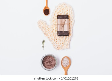 Natural beauty products and accessories for cleansing and exfoliating dead skin cells. Rough washcloth, soap, coffee scrub with sea salt and rosemary oil, flat lay on white background.