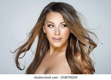 Natural beauty and skincare concept. Portrait of beautiful female model with clean face isolated on grey background. Young woman shows healthy sensitive skin after using cosmetics and makeup.