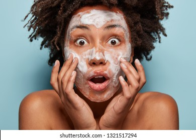 Natural beauty treatment concept. Shocked dark skinned woman washes skin, has soapy face, problems with skin, shows bare shoulders, isolated over blue studio wall. Lady with cleansing foam indoor