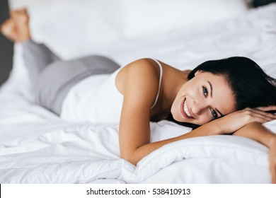 Natural beauty. Young woman looking at camera and smiling while lying on the bed at home