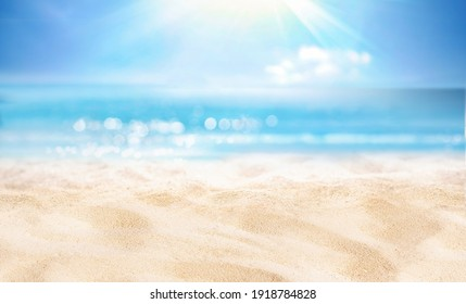 Natural blurred defocused background for concept summer vacation. Nature of tropical summer beach with rays of sunlight. Light sand beach, ocean water sparkles against blue sky. - Shutterstock ID 1918784828