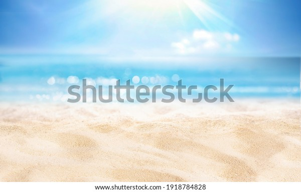 Natural blurred defocused background for concept summer vacation. Nature of tropical summer beach with rays of sunlight. Light sand beach, ocean water sparkles against blue sky.