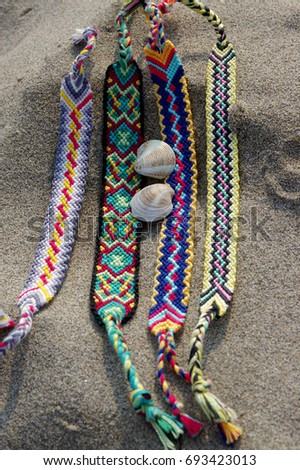 Natural bracelets of friendship in a row, colorful woven friendship bracelets, background, rainbow colors, checkered pattern, in the sand on the beach