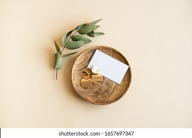 Natural branch with leaves and gold earrings in wooden plate on beige background