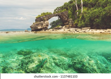 Natural bridge at Neil island, Andaman and Nicobar. Double photo under water and over water. View of the natural bridge, the main attraction of the island against the blue sky. snorkeling, diving
