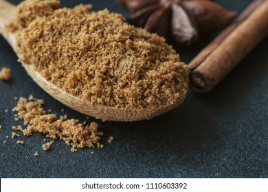 Natural brown sugar or unrefined sugar on wood spoon and cinnamon stick and anise on black granite table with copy space. Sweet seasoning for good health. Ingredient prepared for cooking or bakery.