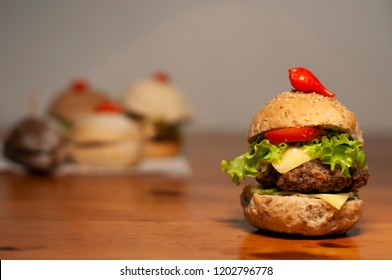 Natural burger on wooden table with bread, oregano, meat, cheese, lettuce, peppermint tomato and potato chips, with sandwiches, blurred in the background.