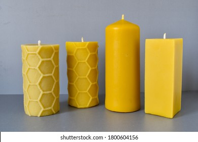 Natural candles made of wax on a gray background, yellow candles in a row, candles on a white background, three candles