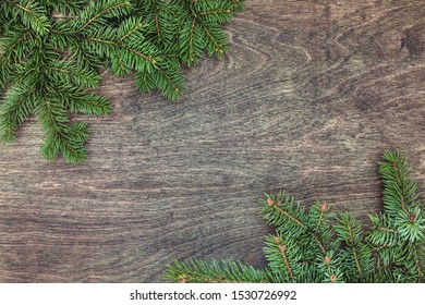 Natural Christmas background with border of fluffy green fir branches on a textured dark brown wood background. Copy space for text, flat lay, top view. Corner frame.