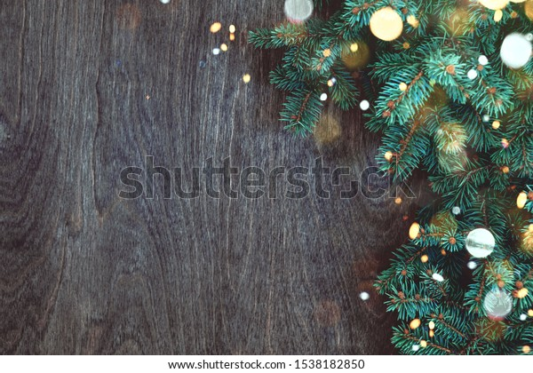 Natural Christmas background with border of fluffy green fir branches on a textured dark brown wood background with christmas lights. Copy space for text, flat lay, top view.
