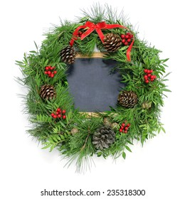 a natural christmas wreath with pine cones, berries and a red ribbon bow and a blank chalkboard on a white background