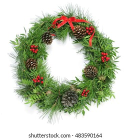 a natural christmas wreath with pine cones, berries and a red ribbon bow on a white background