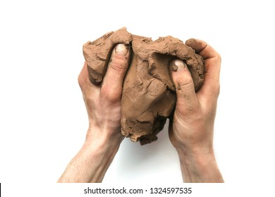 Natural clay piece in hands  isolated on white background.  Wet clay material for sculpting or modeling.