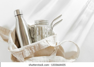 Natural color eco bag with reusable metal water bottle, glass jar and straw. Zero waste. Sustainable lifestyle concept.