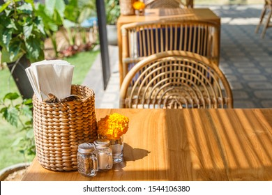 Natural color wooden and rattan furniture at an outdoor cafe. Blue cushions, fresh Marigold flowers, thatched tissue holders. Sunny morning.