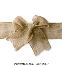 A natural colored burlap ribbon is tied in a bow as if wrapped around a Christmas present, isolated on a white background, with vertical copyspace